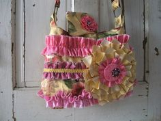 Shabby chic vintage handbag. One of a kind ruffled handbag with 2 pockets inside including a zipper compartment and 1 pocket on the outside with glitzy bead trim and magnetic snap.  Comes with smaller matching bag to hold coins or credit cards. Perfect for spring this bag is pink, yellow, with a touch of green, and has a stunning flower design on the front with a vintage brooch.    More detailed photographs can be found at http://myvintagecouture.imall21.com/0286-handbag/