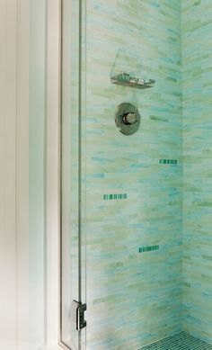 Gorgeous shower with Waterworks Repose Staggered Mosaic Tile in Bliss and Cucumber. The shower features seamless glass shower doors.