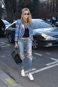 Gigi styled boyfriend jeans and sneakers with a statement jacket — and statement shades to match.