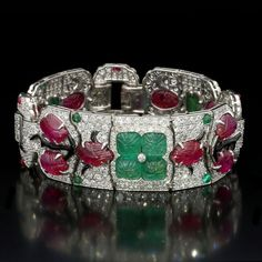 AN EXCEPTIONAL ART DECO DIAMOND, RUBY, EMERALD AND ENAMEL 'TUTTI FRUTTI' BRACELET, BY CARTIER, NEW YORK, 1929  The highly articulated geometric strap-style bracelet pavé set with old and single-cut diamonds against which a vine motif in black enamel, carved rubies and emeralds is laid, all mounted in platinum to a concealed clasp.