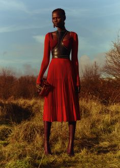 A crimson, fine-knit, ruffled and pleated dress is worn with a black Art Nouveau harness edged with antique gold studs. From the Alexander McQueen Autumn/Winter 2018 pre-collection.