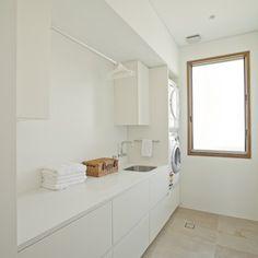 Modelo de cuarto de lavado lineal, actual, grande, con fregadero de un seno, armarios con paneles lisos, puertas de armario blancas, encimera de terrazo, paredes blancas, suelo de piedra caliza y lavadora y secadora apiladas