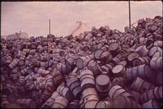 A MOUNTAIN OF DAMAGED OIL DRUMS NEAR THE EXXON REFINERY: Yet another dirty, costly expense of fossil fuel. Photo: John Messina. Environmental Protection Agency. (1972) http://commons.wikimedia.org/wiki/File:A_MOUNTAIN_OF_DAMAGED_OIL_DRUMS_NEAR_THE_EXXON_REFINERY_-_NARA_-_546000.jpg