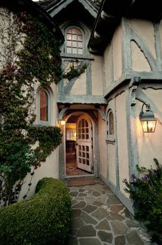 This Tudor style house has a flag stone walkway and very old door .