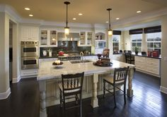 kitchen... hardwood floor with white cabinets and crown moulding