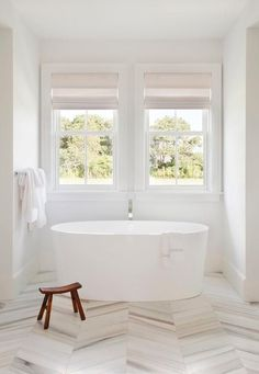 An oval freestanding bathtub sits on gray and white marble herringbone floor tiles in a nook beneath windows dressed in cream roman shades.