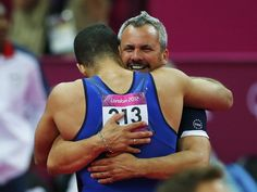 Yin Alvarez, stepfather and coach of Danell Leyva of the U.S., embraces him after he competed in the horizontal bar during the men's individual all-around gymnastics final in the North Greenwich Arena