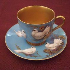 Circa 1919. Royal Worcester demitasse cup and saucer with hand painted decoration by William Powell showing white fantailed doves on a pale blue ground with gilt highlights and borders.