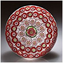 """Parabelle Glass spaced concentric paperweight with a central red rose encircled by red bellflower/yellow rose  complex canes, and assorted millefiori on upset muslin. Signed. Artist's proof. Diameter 3 1/8""""."""
