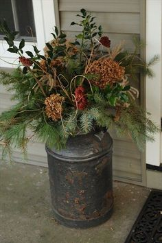 Galvanized milk can with seasonal greenery and flowers.