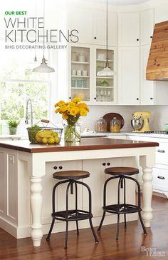I love the island legs! An island with a walnut top is the center of this quaint kitchen. Salvaged heart pine planks cover the vent hood and contrast all-white cabinetry. Industrial-style stools make a unique style statement.