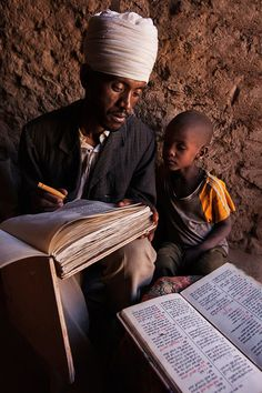 Ethiopian Orthodox priest writing text from the bible on a book made from goat skin - Abi Adi area.
