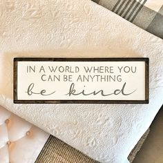 Hand painted wood sign shown: IN A WORLD WHERE YOU CAN BE ANYTHING - BE KIND SIZE: 9x25 COLOR: OFF WHITE FRAME: BLACK PRODUCT DETAILS MATERIAL: WOOD & MINERAL PAINT MADE TO ORDER: SHIPS 2 WEEKS FROM TIME OF PURCHASE HANGING HARDWARE INCLUDED HANDMADE & PAINTED IN MN - Therefore