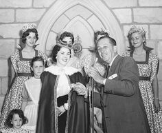 Shirley Temple is all grown up here with Walt Disney, but that didn't stop her from playing kid again at the April 1957 official opening of Disneyland's interior castle.  Here she is with her children, Walt Disney and some of the park's ladies in waiting at the special event, during which she told the story of Sleeping Beauty.  Temple has further ties to Disney's history, having presented Walt Disney with his special Oscar for Snow White and the Seven Dwarfs.