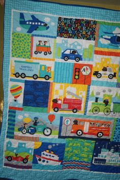 This colorful quilt shows a airplane, wagon, helicopter, tractor, police car, fire truck, train, school bus, cruise ship, motorcycle and race car.