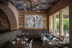 Eclectic Restaurants - A brick arch near a ceiling mural, artwork, and tufted leather banquettes at the Distrit Miami