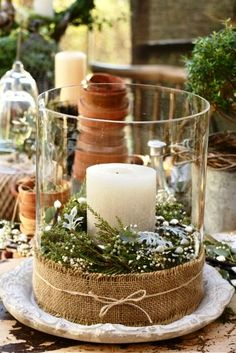 Glass hurricane jar, glue burlap to the bottom, place candle of your choice in middle of glass jar, fill with flowers and clipping of your choice. Very easy and nice decor piece. You can even change it for the seasons.