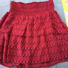 Old Navy Flowy Skirt The color is burgundy mixed with pink shades. It's in great conditions and perfect for the spring or summertime! The skirt also has ruffles and an elastic waistband. Not from Brandy Melville. Brandy Melville Skirts