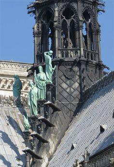 Flèche de la cathédrale Notre Dame de Paris Les quatre grandes statues de cuivre oxydé, couleur vert-de-gris,Trois apôtres sont représentés, dont l'évangéliste Saint Jean sous la forme d'un aigle, représentation classique tirée du tétramorphe de l'Apocalypse. La quatrième statue, celle du haut, est tournée vers la flèche et représente notre architecte Eugène Viollet-le-Duc qui contemple son oeuvre.