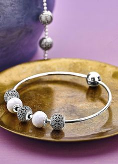 Style the PANDORA ESSENCE COLLECTION bangle with silver and white charms for a modern bohemian look. #PANDORAessencecollection #Patience #Compassion