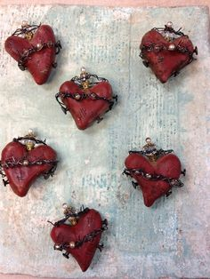 Sacred Heart by Ruth Rae. These were hand-sculpted paper clay, then painted before dipping in wax and then  nails, beads and wire were added.