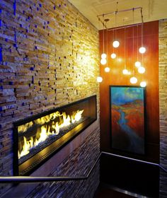Feature Wall A restaurant has taken slate and stone right to the edge of the fireplace frame and used a larger stone at the base to create a faux hearth. #indoor #design #fireplace
