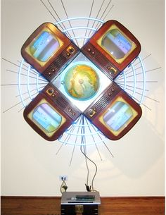 A conceptual video sculpture by Nam June Paik, Polaris (1990) is composed of four televisions arranged like petals around a globe and backlit by concentric neon florescent tubes #neon