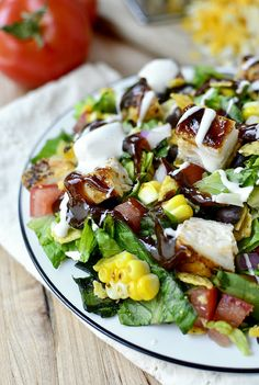 BBQ Chicken Chopped Salad - BBQ chicken and corn, tossed with black beans, Monterey Jack cheese, lettuce, tomato, and red onion. Drizzle with Ranch dressing and BBQ sauce.