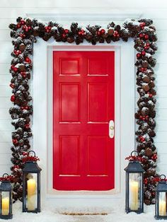 Transform Premade into One-of-a-Kind secured with hot glue coordinate with this red front door, adding bright pops of color to a premade pinecone garland. Tall lanterns, adorned with small sprigs of berries, add to the colorful Christmas door decorations.