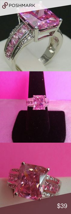 7 CTs Emerald Cut Pink, White CZ's. Size 8. Brilliant,  emerald cut 7 CT Pink AAA rated CZ's. Set in Platinum Plated silver band. Smaller pink cz's and white cz's down each side as seen in pictures. Size 8. Jewelry Rings