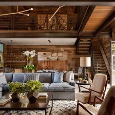 In the main living room of a Connecticut barn, a pair of chairs by Gio Ponti were reupholstered with shearling and a subtly patterned sofa adds contrast in the wood-clad space.