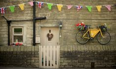 Tour de France excitement is building in Yorkshire ahead of next weekend's Grand Depart as a yellow bicycle hangs from the wall of a stone cottage in Holmfirth. The people of Yorkshire are preparing a grand welcome as the route of stages one and two are decorated with bunting, bikes and yellow jerseys.