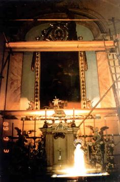 This is a photo of an apparition of the Blessed Virgin Mary. It was taken on September 3, 1989 when an art restorer asked someone to take a picture of him on the scaffolding as he was working on a painting behind the altar. When he turned around, he saw the glowing figures of what looked like the Blessed Mother and a small child. The photographer did not see this vision, yet it appeared in the resulting photograph.
