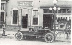 """Below is one of the first retail stations located in a """"hole in the wall"""" in Waycross, GA. In 1915. You can barely see the crown flange next to the left window. Equally important, notice the filling station sign above the door. This is another early sign used by KYSO. The car at the curb is said to be a 1910 EMF."""