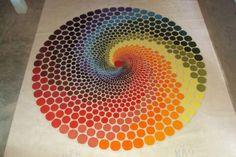 Realizar una espiral utilizando círculos de diferentes tamaños y colores creando un efecto visual de profundidad y perspectiva.