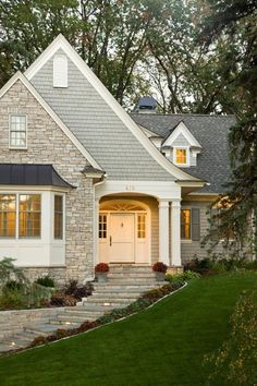 Front window, stone, painted shingle siding, ivory trim, dormers in back, front porch columns