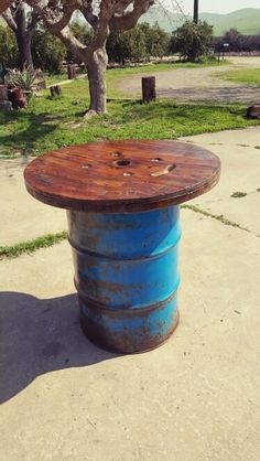Pub table from a wood spindle and 50 gal old barrel. Bullet holes and all!