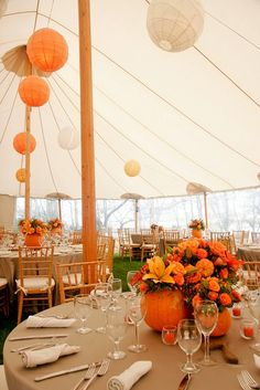 Pumpkin-as-container centerpieces with lilies, roses and hypericum berries. Great for an autumn harvest wedding.