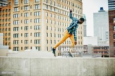 Stock Photo : Man walking along rooftop ledge of building