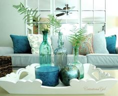 A fresh blue living room with a Pier 1 Antiqued White Scalloped Tray and Teal Velvet Pillows