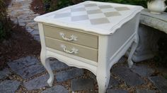 This is DIY chalk paint in Behr's Cottage White. The drawer and harlequin pattern are painted in Annie Sloan's Country Grey.