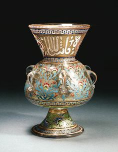 AN ENAMELLED CLEAR GLASS MOSQUE LAMP  20TH CENTURY  Of typical Mamluk form with sloping rounded body and flaring mouth on spreading trumpet foot, six simple loop handles around the body, the surface enamelled in various colours with a band of Iznik style carnation floral sprays, the neck with a band of white stylised naskh calligraphy interrupted by cusped carnation spray cartouches, the foot with a band of scrolling flowering vine, minor meandering bands  11in. (28cm.) high