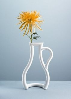 """""""A novel interpretation of the classic vase, this porcelain outline of the familiar shape creates an interesting floral display"""""""