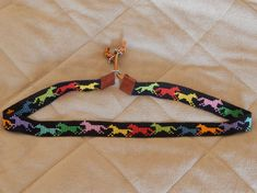 Horses of many colors! This hatband was made with 11/0 beads. It measures 22 of beading and 24 from leather end to leather end. The bead slide allows for further extension. Black background with many different colors of running horses. Thank you for looking