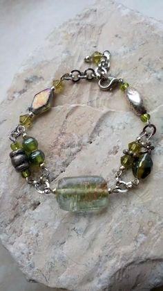 Armband gemaakt met glaskralen in groentinten en metalen onderdelen.