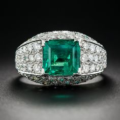 2.50 Carat Emerald and Pave' Diamond Ring in Platinum. This splendid, high-profile emerald and diamond head-turner glistens and glows from every angle. A beautiful, bright-green, almost square-shape, Colombian emerald, weighing two-and-a-half-carats, is comfortably ensconced in a glittering platinum mounting, ablaze with 3.00 carats of bright-white sparkling diamonds.