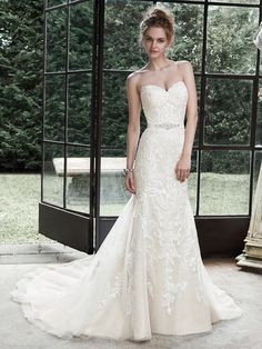 Maggie Sottero - Winstyn Dreamy lace and tulle combine to create this elegant fit and flare wedding dress; accented with timeless sweetheart neckline. A glittering Swarovski crystal motif on an optional grosgrain ribbon belt adds a touch of drama. Finished with covered buttons over zipper and inner elastic closure.
