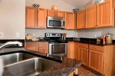 Kitchen with granite countertops, stainless steel appliances and hickory wood cabinets.