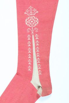 Detail, pair of woman's stockings, England of France, 1750-1770. Frame-knitted salmon-pink silk with decorative clocks worked in ivory silk with sprigs, roses and crowns, stripped upper edge.