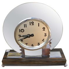 The clock has a round mirror shape, with zig zag motif and stylized Art Deco face/numbers. Description from 1stdibs.com. I searched for this on bing.com/images